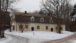 Ett gult och vitt stenhus i Fiskars där det bland annat finns en ungdomsgård.