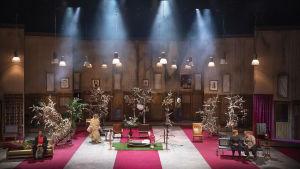 Iso huone, jossa on punavalkoinen matto, nojatuoleja ja sohvia, joilla istuskelee ihmisiä. Näyttämöllä on myös useita kirsikkapuita. Kuvassa Chike Ohanwe, Sanna Majuri, Emilia Sinisalo ja Eero Saarinen.