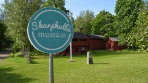 En rund skylt i turkosblått och vitt. Det står Skarpkulla museum på skylten. Bakom finns lador i rött. Sommar och grönt gräs.