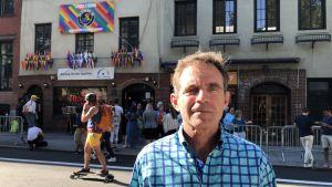 Eric Marcus, med Stonewall-baren och turister utanför, en på rullbräda.