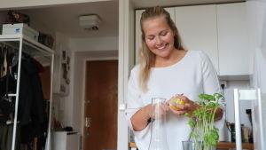 Linda Smids står i en vit skjorta och skär citron i sitt kök i sin etta i Berghäll.