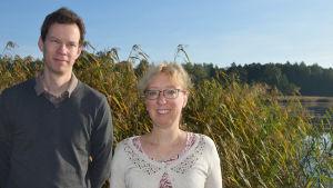 En man och en kvinna vid en vassig havsvik.