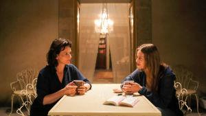 Kaksi naista istuu vastakkain keittiön pöydän ääressä teekupit käsissään. Toinen on n. 45-vuotias ja toinen n. 25-vuotias.