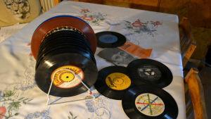 Vinylsinglar, så kallade 45-varvare, ligger på ett bord med fin duk.