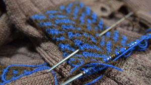 En blå- och brunmönstrad stickning på en trasig brun kofta. Synlig lagning.
