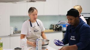 En kvinna med kort grått hår instruerar under en matlagningskurs.