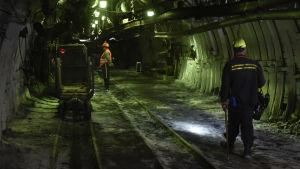 Två arbetare står inne i en mörk kolgruva.