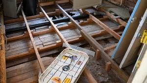 Rum i trähus med borttagna golvplankor.