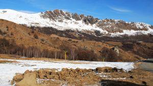 Ett berg med lite snö på sig.