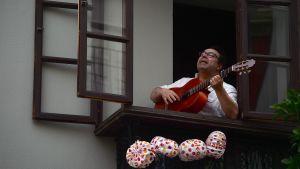 Man sjunger och spelar i ett fönster i Sevilla