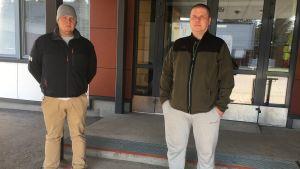Kaksi miestä seisoo koulun edustalla.