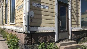 """Hörnet av ett gult gammalt hus i Lovisa med skylten """"Drottninggatan""""."""