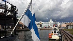 En finsk flagga syns i förgrunden. I bakgrunden Helsingfors.