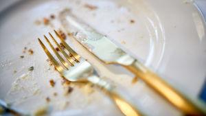 En tom tallrik med matrester och bestick