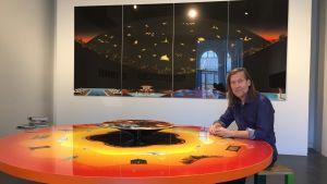 Konstnär sitter vid ett stort orange bord.