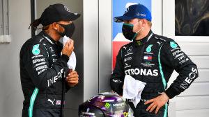 Lewis Hamilton och Valtteri Bottas står och talar med varandra.