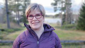 Kvinna i lila jacka och lila glasögon står utomhus och ser in i kameran med ett litet leende.
