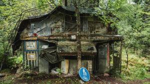 Kaksikerroksinen maja metsässä, edustalla kevyen liikenteen liikennemerkki.