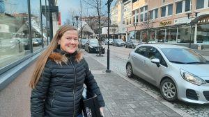 Kvinna med långt hår och svart jacka i stadscentrum.