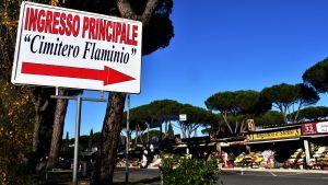 En skylt med texten Cimitero Flaminio. I bakgrunden stånd där det säljs blommor.