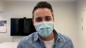 Mansperson med munskydd ser in i kameran. Kontorsmiljö.