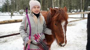 Viola Mäenpää står bredvid islandshästen