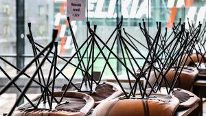 Ett kafé där stolarna har ställts upp och ner på borden.