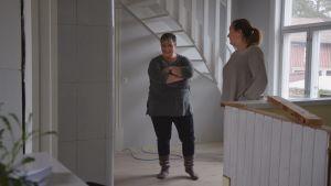 Claire Witick-Mäkelä och Åsa Björkman skrattar i ett rum med vita träväggar.