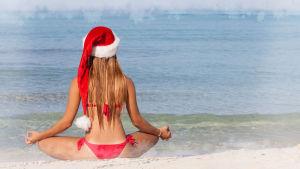 Tonttulakkinen nainen meditoi hiekkarannalla. Katse aavalle merelle.
