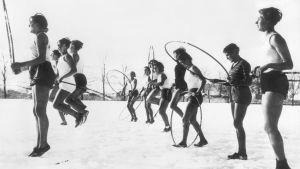 Flickor i Berlin på 30-talet som gör skolgymnastik, utomhus i snön iklädda endast shorts och linne.