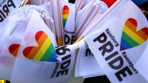 En massa, små vita flaggor där det står Raseborg Raasepori Pride står i ett ämbar.