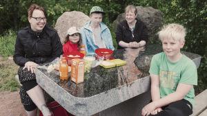 Två vuxna och tre barn har picknick kring ett bord gjort av polerad granit.