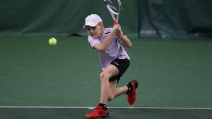 En pojke spelar tennis