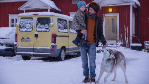 Perustulokokeiluun osallistuva Juha Järvinen pihamaallaan Jurvassa, yhdessä lapsen ja koiransa kanssa.