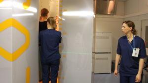 Patient står i ny röntgenapparat vid ÅUCS och får hjälp av två röntgenskötare.