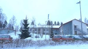 Ett stort grått hus i ett vinterlandskap.