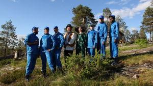 Kahdeksan henkilöä seisoo yhdessä kesäisellä kalliolla hymyillen. Kuudella heistä on sinisen verryttelyasu.