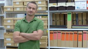 Victor Wilson med arkivmappar och arkivlådor i bakgrunden. Han finns inne i ett arkiv.
