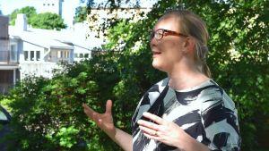 Katja Långvik i profil medan hon talar och ler. Hon är utomhus med ett träd och en byggnad i bakgrunden en varm sommardag i Ekenäs.