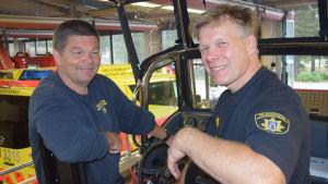 Två leende män sitter i en båt. De är brandmän och sitter bakom ratt och instrumentpanel på en riktigt ny räddningsbåt med tak över förarplats och ratt