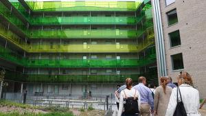 En grupp med folk bekantar sig med bostadsmässans höghus