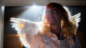 Näyttelijä Mari Perankoski enkelin asussa siivet selässä