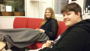 En ung kvinna och man sitter på en röd soffa.