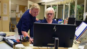 Päivi Granqvist och Carina Karlsson  ser över arbetsschemat vid datorn i Almahemmets kansli.