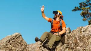 Man sitter på en bergstopp i soligt väder. Han bär en orange t-skjorta och gröna byxor. Han har glasögon på sig som används för at uppleva en virtuell verklighet.
