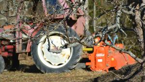 traktor syns genom trädgrenar