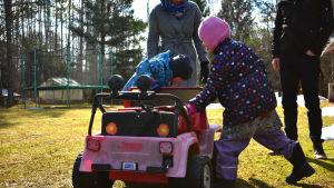 Två barn leker med en trambil ute på en gräsmatta. I bakgrunden en kvinna och en man.