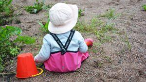En liten flicka sitter med regnbyxor på i sanden med en hink.