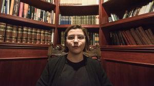Hanna Lagerström sitter svartklädd i en mörk trästol med snirklat ryggstöd. I bakgrunden finns en bokhylla full med böcker.