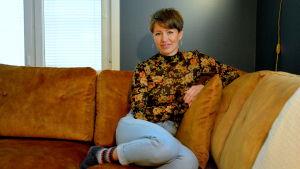 en kvinna i blommig tröja och jeans sitter i en brun soffa